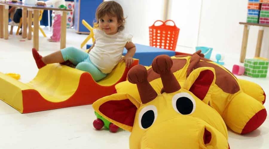 Niña en la ludoteca jugando sobre un sillón de espuma