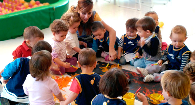 Grupo de alumnos y alumnas de 1 y 2 años junto a su profesora